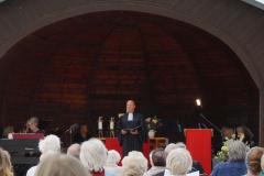 Ein Mann steht im Pavillon vor der Gemeinde.
