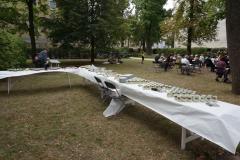 Hinter der Gemeinde stehen Tische mit einem Fingerfood-Buffet. Der Großteil der Speisen ist in kleine Weckgläser abgefüllt.