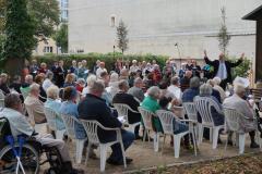 Neben dem Pavillon steht der Chor in lockerer Aufstellung, der zwischen der Gemeinde steht der Kantor und dirigiert die Gemeinde mit großer Armbewegung.