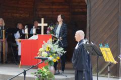 Eine andere Frau steht am Lesepult, vor dem Pavillon steht der Pfarrer.
