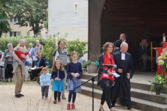 """Mehrere Kinder und Erwachsene gehen vor dem Pavillon entlang. Eine Frau trägt einen Schal mit dem Aufdruck """"Kirche mit Kindern"""" ."""