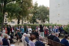 Der Chor singt, eine Frau dirigiert mit großer Geste.