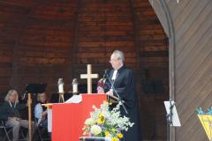 Am Lesepult steht ein Mann, er trägt eine goldene Kette mit Kreuz über dem Talar.