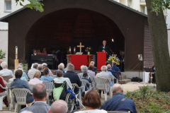 Im Pavillon steht der Bischof am Lesepult, davor sitzt die Gemeinde.