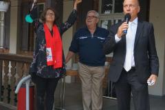 Ein Mann spricht am Mikrofon, eine Frau hält ein orangenes Rohr in die Höhe. Ein weitere Mann steht zwischen ihnen. Alle drei stehen leicht erhöht auf dem Treppenabsatz zum Gemeindesaal.