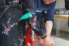 Die Frau und der Mann stecken das Plastikrohr in ein vorbereitetes Loch in der Erde.