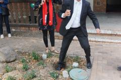 Der Mann mit dem Mikrofon stellt sich mit einem Fuß auf das verschlossene Rohr.