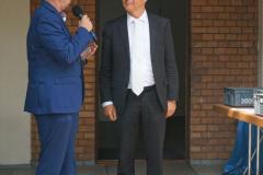 Ein weiterer Mann im blauen Anzug spricht jetzt vom Absatz vor dem Gemeindesaal.