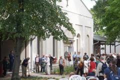 Am linken Bildrand steht der Redner im blauen Anzug, davor der Mann, der die Zeitkapsel mit Erde bedeckt. Auf der rechten Seite des Bildes stehen viele Personen, die zuhören und zuschauen.