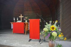 Im Pavillon stehen Altar, Lesepult und Blumenschmuck. Die Paramente sind rot.