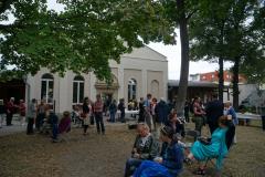 Auf dem Rasen vor der Kirche stehen und sitzen viele kleine Grüppchen. Die Personen unterhalten sich.