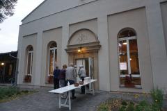 Personen stehen vor dem Kircheneingang und registrieren sich für die Veranstaltung