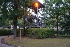 Die Glocken im frei stehenden Glockenturm schwingen, die Außenbeleuchtung am Turm ist bereits an.