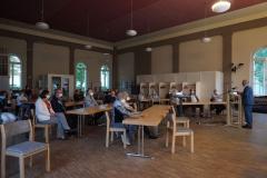 Im Kirchsaal sitzen Personen mit Abstand an Tischreihen und schauen zum Redner.