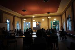 Blick aus dem Hintergrund durch den abgedunkelten Saal. Auf der Leinwand ist ein Bild von Friedrich dem Großen zu sehen. Er scheint skeptisch in den Saal zu schauen.