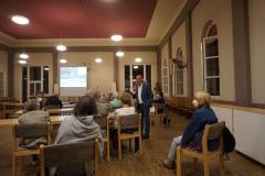 Der Kirchsaal ist wieder beleuchtet. Ein Mann steht mit Mikrofon in der Hand an der Seite einer Tischreihe. Er schaut eine ältere Person an, während er spricht.