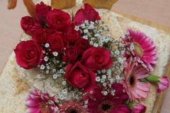 """Blick von oben auf eine rechteckige Torte. Sie ist zweistöckig, der obere Teil ist klein und rund. Hinter dem Aufsatz steckt """"100"""" in großen, goldenen Ziffern. Auf dem Aufsatz ist ein Kreuz mit roten Rosen gesteckt, die Kante zum unteren Teil mit weiteren roten und rosafarbenen Blüten verziert."""