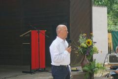 Ein Mann in weißem Hemd steht vor dem Pavillon. Hinter ihm ein Rednerpult mit rotem Banner, daneben Blumen.