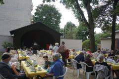 Vor dem Pavillon stehen lange Tischreihen mit gelber Tischdecke. Auf den Tischen stehen Tassen und Kaffeekannen.