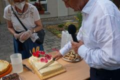 Ein Mann mit Mikrofon in der Hand schneidet durch die verzierte Torte.