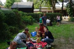 Mehrere Familien sitzen mit ihren kleinen Kindern auf Picknickdecken.