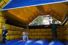 Mehrere Kinder springen und laufen in einer Hüpfburg.