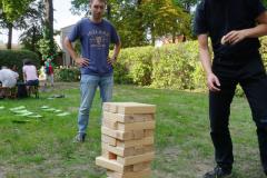 Zwei junge Männer spielen mit einem großen Jenga.