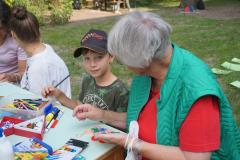 Ein Junge sitzt an einem Tisch und hält einen Stift in der Hand. Neben ihm sitzt die Großmutter, sie hält Aufkleber in verschiedenen Formen aus Glitzerfolie in der Hand.