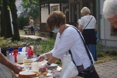 Eine Frau steht hinter dem Kuchenbuffet und legt ein Stück Kuchen auf einen Teller.