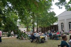 Auf dem Rasen vor der Kirche stehen weitere Tische, an denen Personengruppen sitzen.