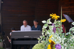 Zwei Männer sitzen am elektronischen Klavier, im Vordergrund sind Blumen.