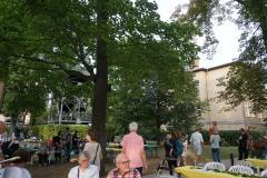 Die Glocken im Glockenturm im Hintergrund sind in Bewegung, auf dem Weg stehen mehrere Eltern mit Kindern, die die Glocken beobachten.