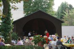 Im Pavillon steht ein Mann am Lesepult, davor sitzen viele Gäste an den Tischen.