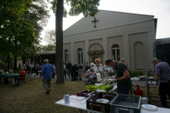 Vor der Kirche steht ein Grillbuffet, eine lange Schlange wartet davor.