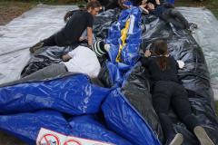 Auf einem großen, schwarz-blauen Packen aus Gummi liegen mehrere Jugendliche.
