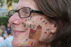 """Auf die Wange einer Frau ist eine Kirche gemalt, darüber der Schriftzug """"100 Jahre""""."""