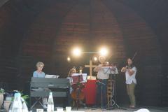 Im Pavillon stehen vier Personen und musizieren an Klavier, Cello und zwei Geigen.