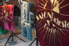 """Drei Notenständer sind in Nahaufnahme zu sehen. An ihnen hängen  Banner aus Samt in unterschiedlichen Farben, die das Logo und den Schriftzug """"Salonorchester Berlin"""" tragen.mit"""