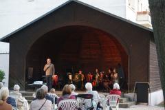 Im Pavillon sitzt das Orchester, am Mikrofon steht ein Mann und spricht.