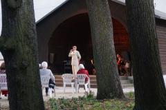 Zwischen drei Bäumen hindurch sieht man einen Mann im Pavillon stehen. Er ist in beige und im Stile der 1920er gekleidet.
