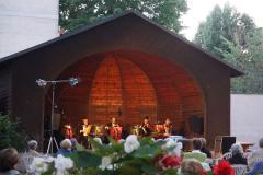 Im Pavillon sitzt das Orchester, in der Dämmerung beginnt die innen angestrahlte Holzmuschel in warmen Ton zu leuchten.
