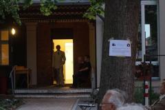 Vor der offenen Tür zum Gemeindesaal und von hinten beleuchtet steht der Sänger des Orchesters.