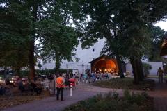 Der innen beleuchtete Pavillon steht in der Dämmerung zwischen den alten Bäumen. Davor sitzt das Publikum, sowohl auf dem befestigten Platz als auch auf der Wiese dahinter.