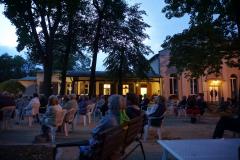 Beim Blick seitlich  über das Publikum sieht man das beleuchtete Gemeindezentrum in der Dämmerung.